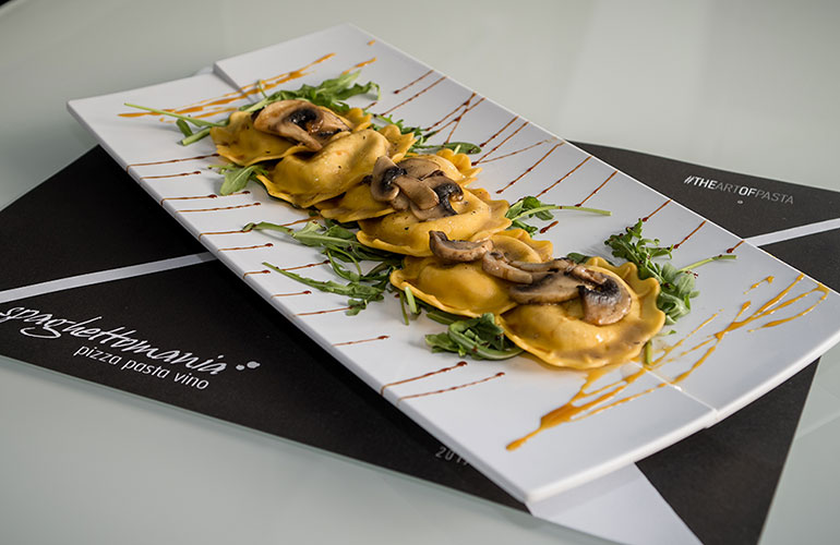 Fresh handmade raviolis filled with nuts and cheese, served with mushrooms and forest fruits Balsamic