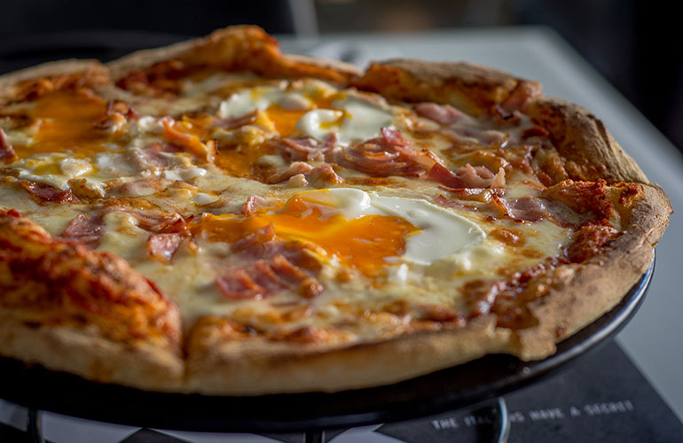 Handmade pizza with tomato sauce, mozzarella cheese, bacon and egg